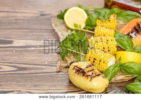 Corn Baked In Olive Oil, With Pepper, Salt And Basil On Blue Dish On A Black Stone Surface. Vegetari