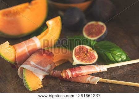 Cantaloupe Melon Sliced With Prosciutto Jamon, Basil Leaves, Fig And Dried Cherry. Italian Appetizer