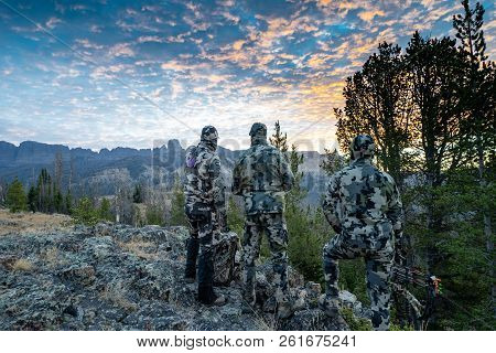 Three Adult Male Hunter Friends, Unrecognizable,  Stand On A Mountain Ridge Looking For Elk To Hunt