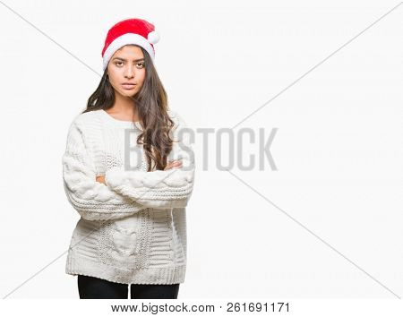 Young arab woman wearing christmas hat over isolated background skeptic and nervous, disapproving expression on face with crossed arms. Negative person. poster