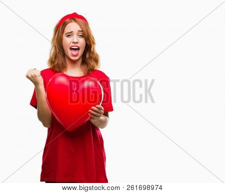 Young beautiful woman holding red heart in love over isolated background screaming proud and celebrating victory and success very excited, cheering emotion