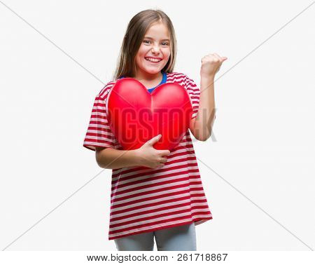 Young beautiful girl holding red heart over isolated background screaming proud and celebrating victory and success very excited, cheering emotion