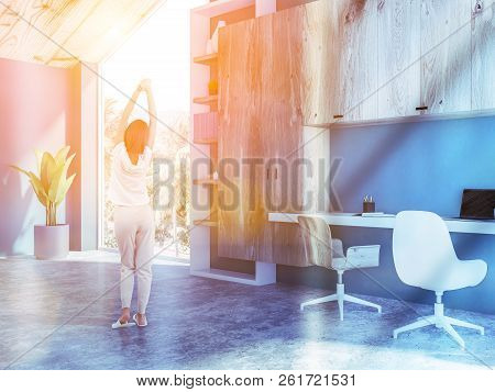 Rear View Of Young Woman In Pajamas Standing Near Computer Desk Of Her Home Office In The Morning. S