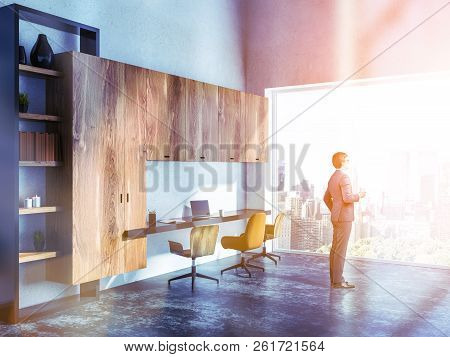 Side View Of Young Buisnessman With Coffee Looking In His Home Office Window. White Walls And Stylis