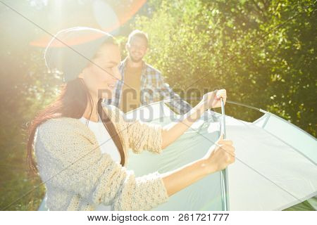 Happy young couple of trippers putting tent in the forest on sunny day to have some rest