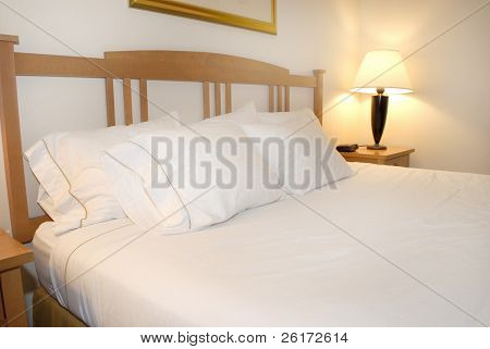 Group of several white pillows on a bed with headboard