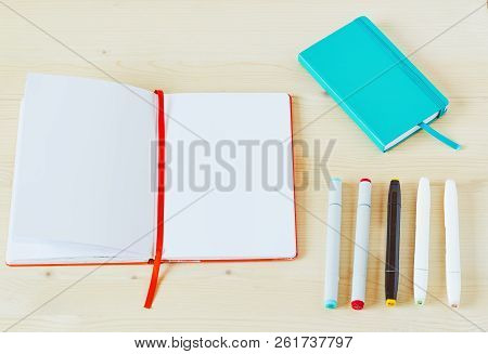 Photo Of Open Sketchbook With White Copy Space On Light Wooden Table. With Five Markers And A Teal S
