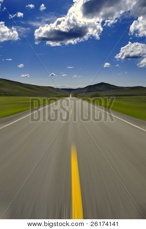 Road with blue sky and clouds blurry motion to indicate speed