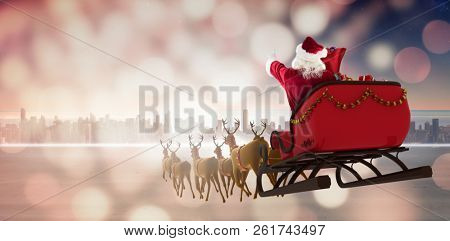 Santa Claus riding on sleigh during Christmas against beautiful landscape of an urban city