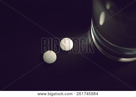 White Pills With Glass Of Water On Dark Background, Insomnia