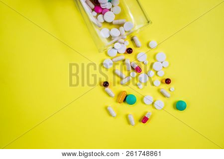 Pharmaceutical Pill Medicine, Multivitamin And Colorful Antibiotic Pill Medicine On Yellow Backgroun