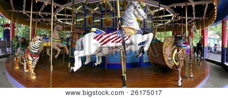 Carousel at amusement park with rides for kids