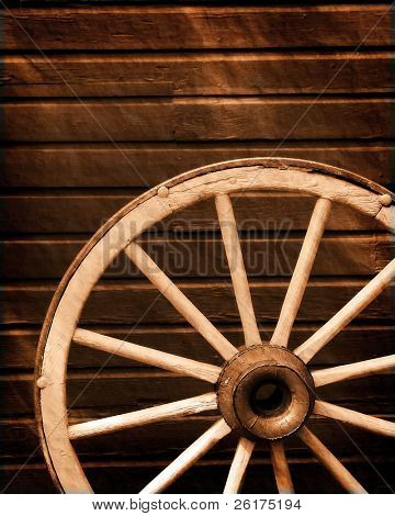 Antique wagon wheel leaning against old wooden wall