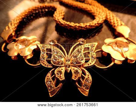 Warm Close Up Image Of Glittering Gold Jewelry Of Diamonds Studded Butterfly With Gold Flowers On Ei