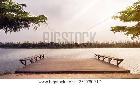 The River And Wooden Pier Stretching Into The Lake At Dawn In The Morning.