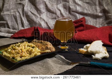 Pasta with delicious, juicy fish, beer and bread on wooden background poster