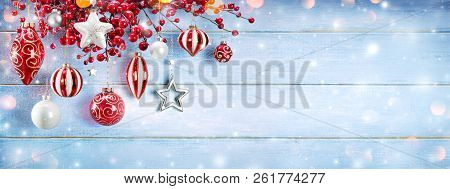 Christmas Ornaments And Berries Hanging On Snowy Wooden Plank