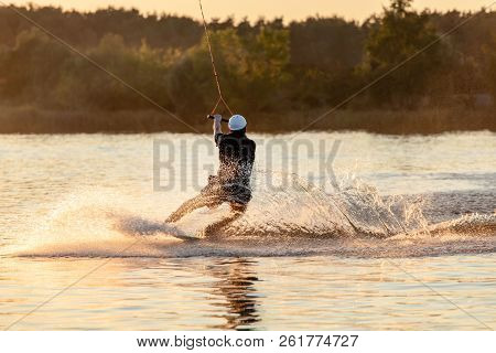 Wake Board A Man Does A Trick At Sunset On The Board On The Water Splashes