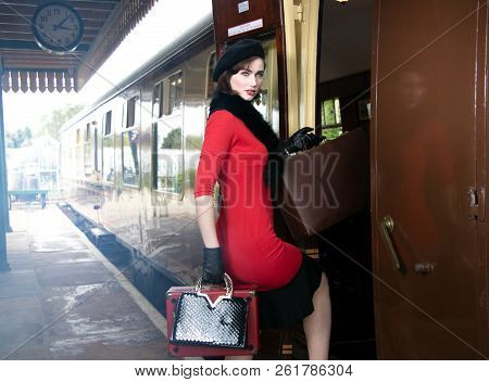 Vintage Attractive Female Wearing Red Dress And Black Beret With Suitcases On Platform Of Train Stat