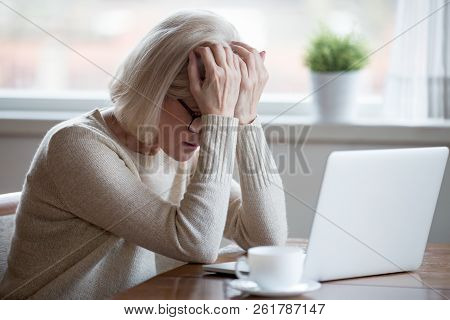 Middle-aged Woman In Front Of Laptop Frustrated By Bad News