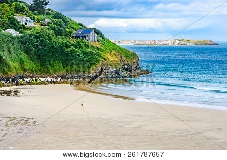 Sandy Beach, Cliff And See In Cornwall. Tranquil Setting With Figure Walking Pin Beach
