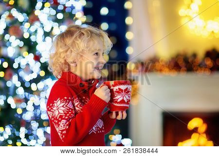 Kids At Christmas Tree. Children Drink Hot Cocoa.