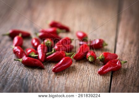 Close Up Of Red Chillies On Wooden Background. Shallow Depth Of Field.