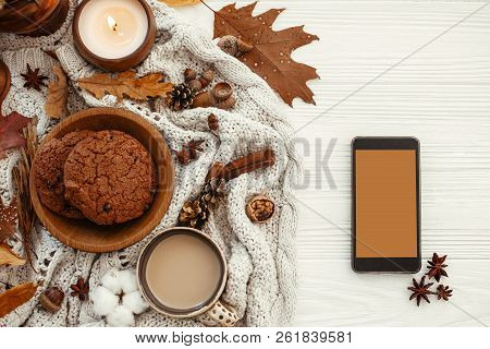 Stylish Autumn Flat Lay. Phone With Empty Screen And Coffee,cookies, Leaves, Candle, Nuts, Acorns, C
