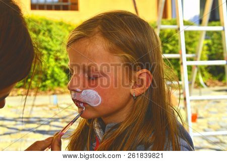 Woman Painting Face Of Kid Outdoors. Baby Face Painting. Little Girl Getting Her Face Painted Like A
