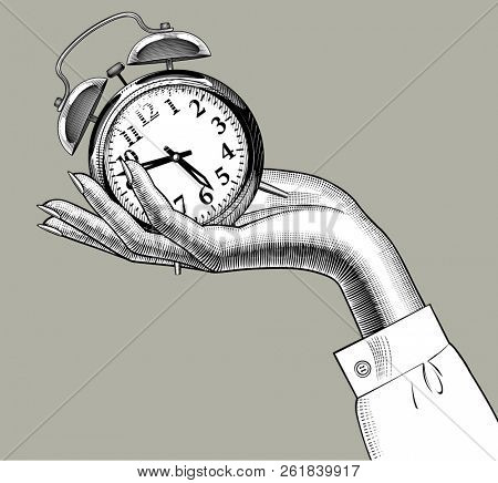 Female hand holding on the palm a retro alarm clock. Vintage engraving stylized drawing