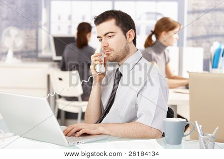 Young office worker sitting at desk in office, talking on phone, using laptop, women working in the background.?