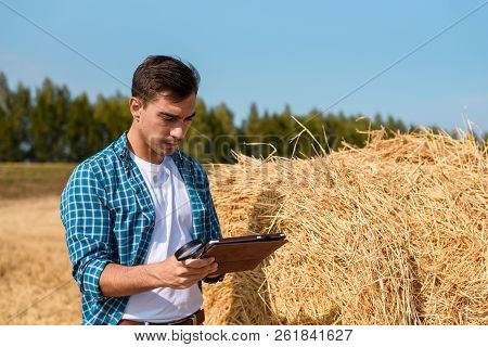 Young farmer with tablet next to a haystack in the field, harvest, industry, farming, valuation, business poster