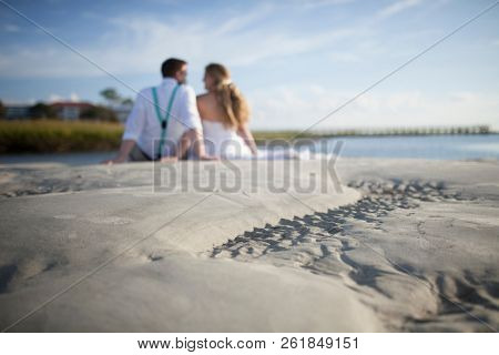 Newly married couple seated on beach, out of focus in background with focus on ripples in sand.
