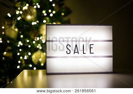 Winter And Shopping Concept - Lihtbox With Sale Word In Dark Room With Decorated Christmas Tree