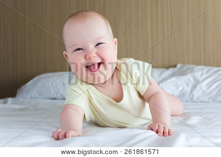 Portrait Of Funny Little Baby Girl Lying On The Bed