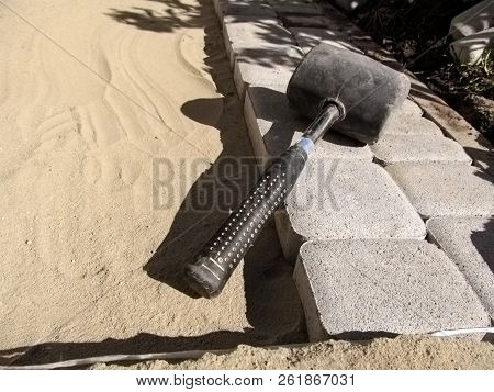 Smooth Rows Of Gray Paving Slabs On The Clean Sand And Black Rubber Mallet Close Up. Construction Ba