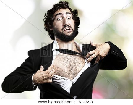 business man with courage and superman concept tearing off his shirt against a abstract background