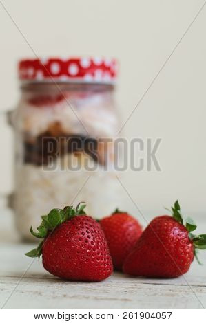 Vertical Photo Of Fresh Strawberry And Jar With Overnight Oats On White Wooden Table