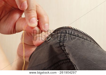 Hands Of Clothier Sew Cotton Clothes With A Needle Close Up