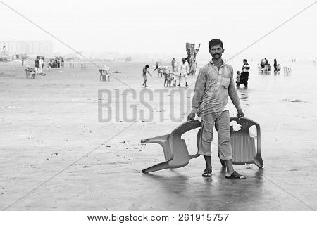 Man Standing On Beach Holding Chairs At Clifton, Karachi, Pakistan 29/06/2012