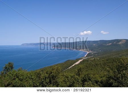 Sheltered bay and beach, viewed from a hillside, with bright blue summer skies and a wandering road in the foreground; Cape Breton, Nova Scotia, Canada