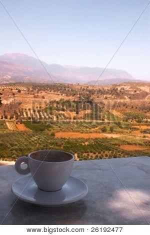 Una taza de café vacía sobre una mesa en el sitio arqueológico de Festos, con vistas a la llanura de Mesara