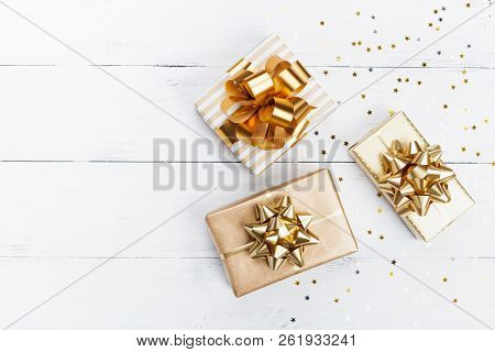 Heap Of Gift Or Present Boxes And Stars Confetti On White Wooden Table Top View. Flat Lay Compositio