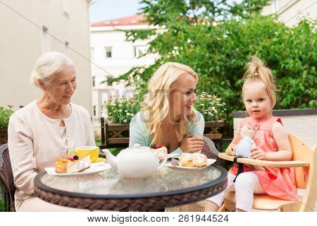 family, generation and people concept - happy smiling woman with daughter and senior mother at cafe or restaurant terrace