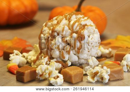Close Up Of A Popcorn Ball With Caramel On A Fall Background