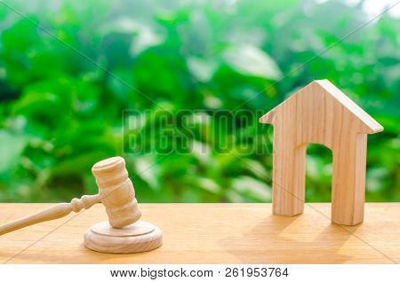 Wooden House And Hammer Of The Judge On A Green Background. Concept Trial Property. The Court Decisi