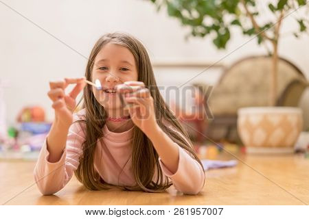 Girl Playing With Matches. Dangerous Situation At Home. A Small Child Plays With Matches, A Fire, A