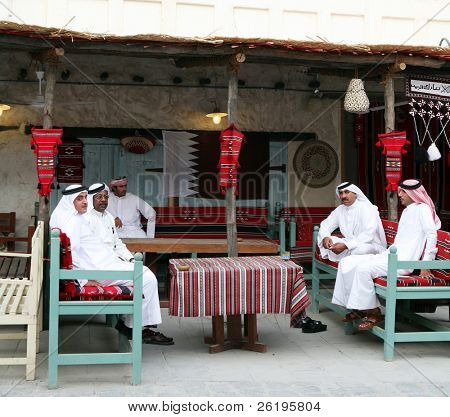 Qatari Arab nationals relaxing at a traditional coffee shop in the Old Souq, Doha, Qatar. The Qatari flag is on the wall. National dress is normal everyday attire for citizens.