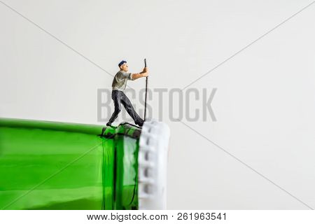 Miniature Man Opening Beer Bottle. Close-up Photo