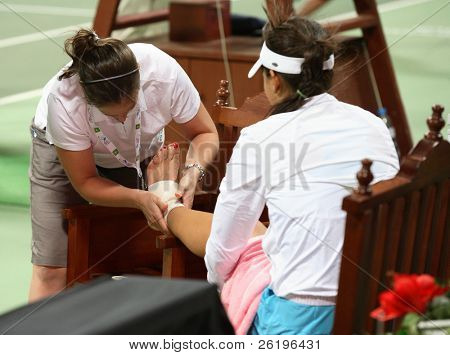 Serbia's Ana Ivanovic has her ankle bandaged after falling on court in the final game of her Qatar Total Open debut against  Olga Govortsova, February 20, 2008.